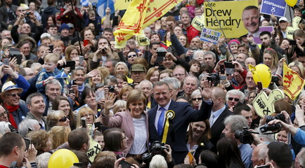 Nicola Sturgeon, the leader of the Scottish National Party, and local candidate Drew Hendry wave to people in the crowd while campaigning in Inverness