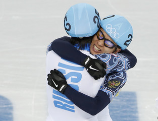 Winner Victor An and second-placed Vladimir Grigorev of Russia celebrate after the men's 1,000 metres short track speed skating final event at the Iceberg Skating Palace during the 2014 Sochi Winter Olympics