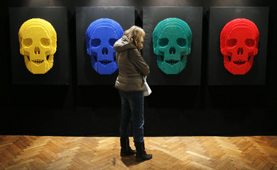 """A visitor looks at the art work titled """"Skulls"""" during the """"The Art of the Brick"""" exhibition in Brussels"""