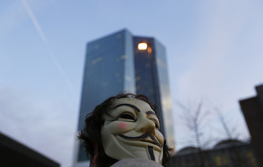 A Blockupy protester with a mask of Guy Fawkes on the back of his head walks at the end of a demonstration against the opening of the new European Central Bank (ECB) headquarters in Frankfurt