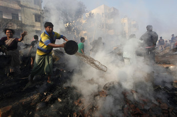 Local resident tries to extinguish a fire at a slum in Kolkata