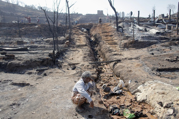 A refugee from Myanmar squats amidst ruins near his home at the Um-Piam refugee camp after a fire engulfed a big part of it near Mae Sot