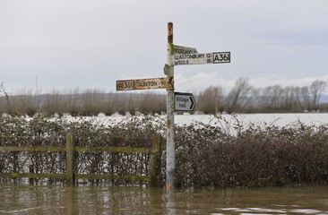 A road sign is surrounded by flood water in the village of Burrowbridge in Somerset in southwest England