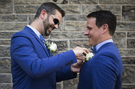"""A couple adjusts each other's boutonniere before """"The Celebration of Love"""", a grand wedding where over 100 LGBT couples got married, at Casa Loma in Toronto"""