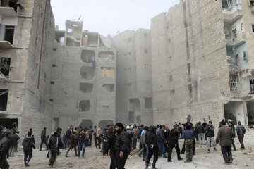 Residents inspect damage after what activists said was shelling by forces loyal to Syria's President Bashar al-Assad in the Dahra Awad neighborhood of Aleppo