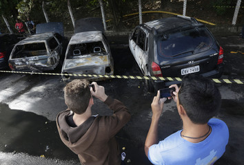Youths take pictures of burned cars near Complexo do Alemao in Rio de Janeiro