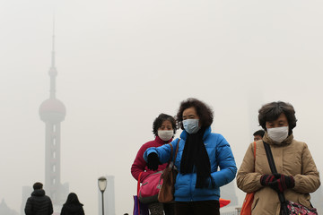 Woman wear face masks on the Bund in front of the Oriental Pearl TV Tower during a hazy day in downtown Shanghai