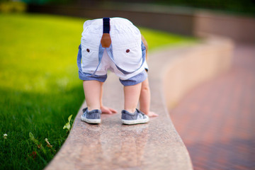 small boy in shorts on suspenders and sneakers climbed onto a shiny granite parapet in the park and turned his booty, getting on all fours