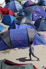 A heart and UK symbol are marked on the side of a tent as a migrant walks in the make-shift camp, called the jungle, in Calais, France, after Britain's referendum results to leave the European Union were announced