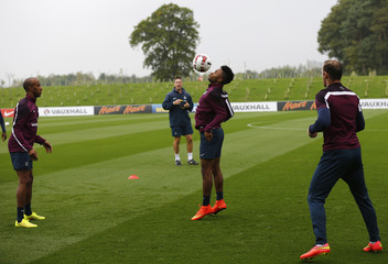 England's Rooney and Delph watch as teammate Sterling controls the ball during a training session at the St George's Park training complex near Burton-upon-Trent