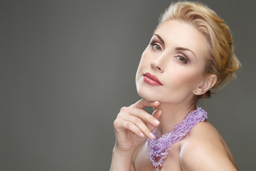 Mature chic. Portrait of a stunning blonde female wearing violet neckpiece looking at the camera touching her face