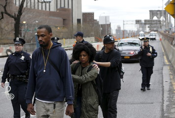 Demonstrators are escorted by the NYPD off the Brooklyn Bridge roadway during a protest against police brutality against minorities in New York