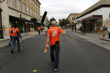 A volunteer carries a broom while joining others in cleaning glass from businesses damaged by Sunday's magnitude 6.0 earthquake in Napa