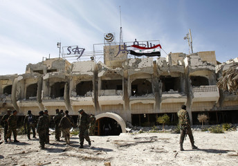 Soldiers loyal to President al-Assad stand outside damaged hotel in Maloula village, northeast of Damascus, after taking control of village from rebel fighters