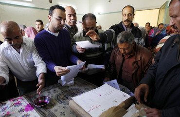 Egyptians cast their vote during a national referendum at a polling station in Cairo