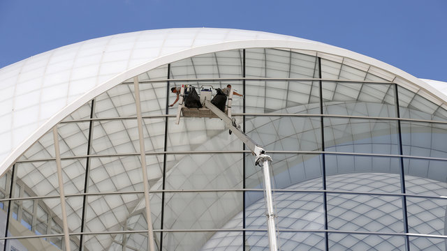 Workers apply tinting to the windows on The United States Institute of Peace building in Washington