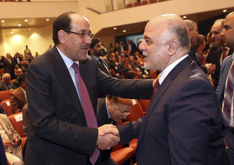 Iraq's Vice President al-Maliki and new Prime Minister al-Abadi shake hands during the session to approve the new government in Baghdad