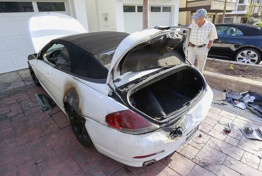 Man looks at a BMW car that was damaged by a lightning strike on Haynes Lane in a residential area of Redondo Beach