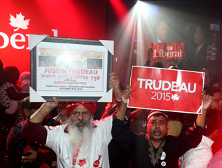 Liberal Party supporters hold up signs as they watch results during Canada's federal election in Montreal