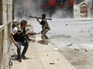 A Free Syrian Army fighter prepares to fire a RPG as Syrian Army tank shell hits a building across a street during a heavy fighting in Salaheddine neighborhood of central Aleppo