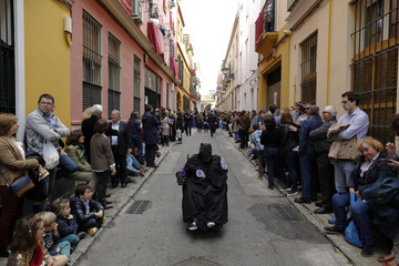 A penitent of the San Bernardo brotherhood takes part in a Holy Week procession in the Andalusian capital of Seville