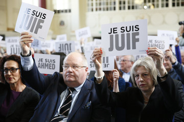 """Britain's Secretary of State for Communities Eric Pickles and Home Secretary Theresa May hold up signs reading """"I am Jewish"""" during a Board of Deputies of British Jews event in London"""