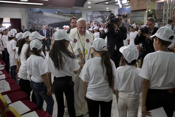 Pope Francis greets children at a meeting in the Phoenix Center of the Dheisheh refugee camp, near the West Bank town of Bethlehem