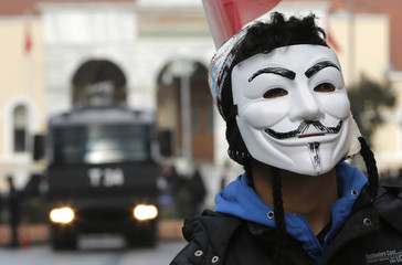 A high school student wearing a Guy Fawkes mask takes part in a protest against the education policies of the ruling AK Party, as a police vehicle is seen in the background, in Istanbul