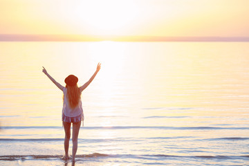 Silhouette of woman wearing hat with open arms under the sunrise near the sea