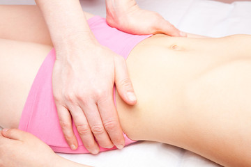 Girl receiving osteopathic treatment of her pelvis