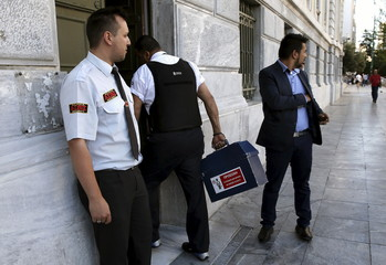 A security guard carries a box with cash into a branch of the National Bank of Greece Athens