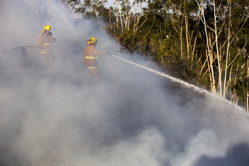 Firefighters spray water to put out a brush fire burning on the eastbound Ventura (134) Freeway in Los Angeles