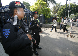 Indonesian Catholics walk past policemen as they enter the gate of Jakarta's main cathedral