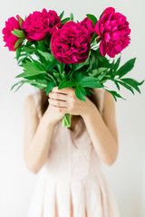Happy young woman holding in hands peony bouquet. Woman in pink dress. Sweet romantic moment