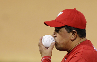Venezuela's President Hugo Chavez kisses the ball during a friendly softball game in Caracas