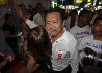 Chuwit Kamolvisit, a former massage parlour tycoon-turned-politician and a candidate for his Rak Prathetthai (Love Thailand) party gets a kiss as he campaigns in Bangkok's notorious Patpong district