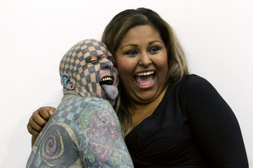 """Matt Gone, also known as """"The Checkered Man"""", poses with a woman during the """"Expo Tatuaje"""" international, a tattoo expo, in Monterrey"""