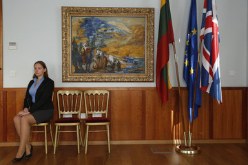 "Embassy intern poses with the artwork ""Landscape of Jerusalem with Bedouins"" by artist Emmanuel Mane-Katz at the Embassy of Lithuania in London"