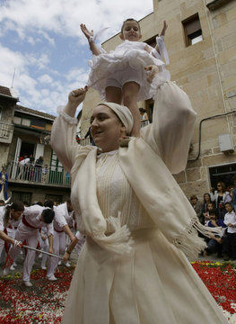 """A five-year-old girl, dressed in a traditional costume called """"Penlas"""", dances on the shoulders of a woman during the """"Coca"""" celebration in Redondela"""