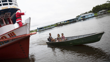 A member of the Amigos do Papai Noel dressed as Santa Claus waves to residents from a boat during a visit to the community Sao Jose in Careiro da Varzea