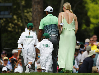 U.S. golfer Woods walks on the first green with girlfriend Vonn and his two children Sam and Charlie during the par 3 event held ahead of the 2015 Masters at Augusta National Golf Course in Augusta