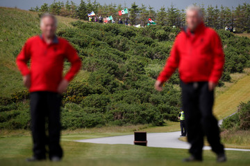 Members of Republican presidential candidate Donald Trump's security team try to prevent photographers from taking photographs of protesters near the golf course at his Trump International Golf Links in Aberdeen