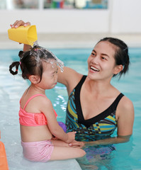 Mother with baby in swimming pool training.