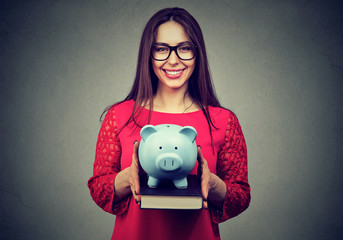 Student, happy woman, holding books and piggy bank in hands