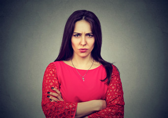 angry woman standing with arms folded on gray background