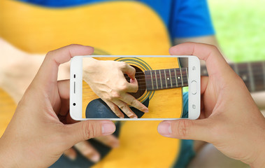 Hands taking picture of man playing guitar with smartphone.
