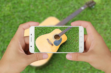 Hands taking picture of guitar on green grass with smartphone.
