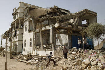 Boys play near a building demolished during recent fighting between government forces and Shi'ite rebels in the northwestern Yemeni city of Saada
