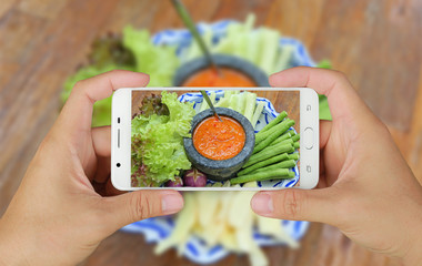 Hands taking picture of chilli crab egg with vegetables with smartphone.