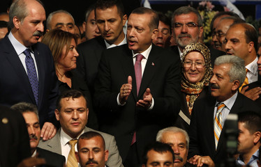 Turkey's Prime Minister and the leader of Justice and Development Party (AKP) Erdogan poses with the new members of his party during a party meeting in Istanbul